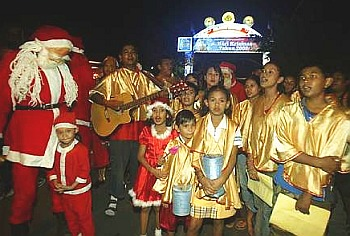 Image: Christmas cheer: Carollers singing festive songs as they visit homes in the settlement on Thursday night.
