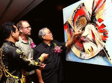 Image: Manyin (right) looking at one of the paintings at the ongoing expo in Sarawak Museum, Kuching, recently while museum director Datuk Sanib Said (left) and Oetelaar look on.