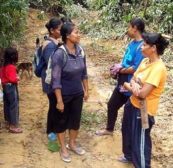 Image: Off we go: The orang asli women visit the forest daily to tap rubber and pick fruits.