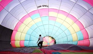 Image: A worker smoothing out the kinks in the canvas for one of the hot-air balloons.
