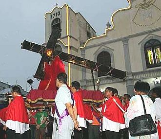 Image: Members of the Irmaos de Igreja carring the statue of Christ carrying the cross.
